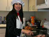 Principal Elizabeth Gonzalez dressed the part and fried the ham. © Denise Gary