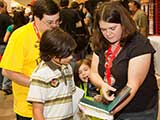 KNTR volunteer Sherrie Miller enjoys new books with her family. © Bruce Matsunaga